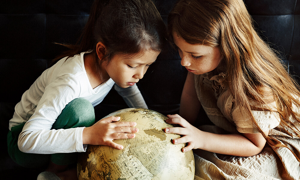 Us Vs Them girls looking at globe